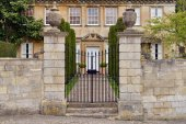 Fotografie View of gateway and exterior stone wall of old English mansion house