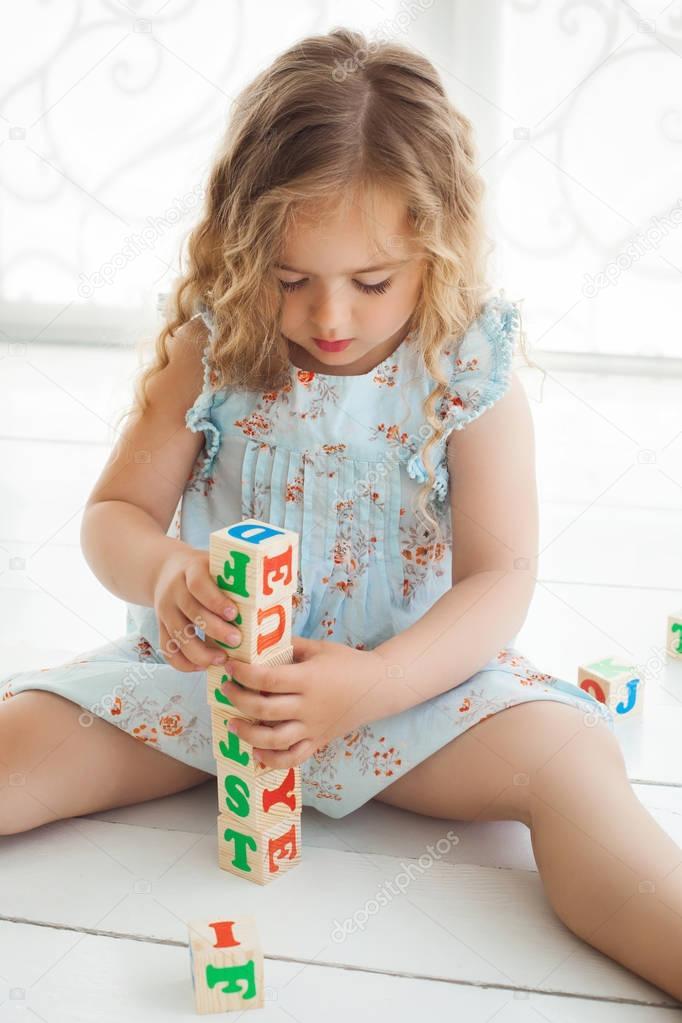 Kleine süße Mädchen spielen mit Abc Würfel und Erziehung