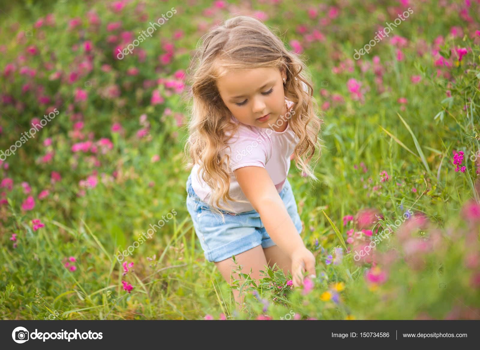 very cute little girl standing in the field of flowers on whild