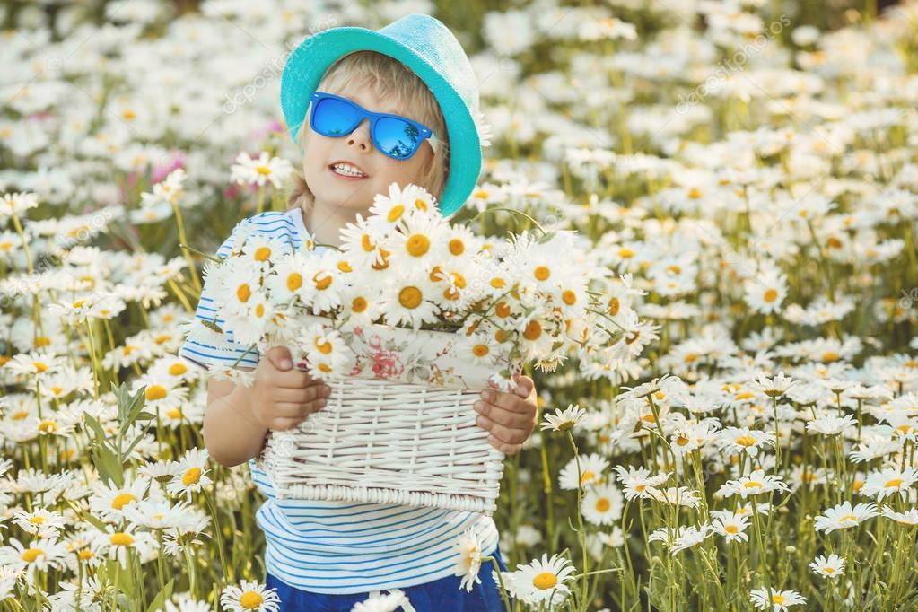 Emotional kid in the camomile field. Cheerful child with flowers