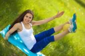 Fotografie junge Frau beim Training mit Fitnessball im grünen Park
