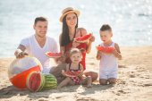 Young parents with children eating watermelon on beach