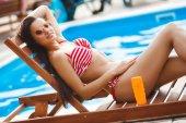 nő a csíkos bikini a fényvédő közelében uszoda, szolárium szalon