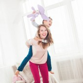 Fotografie Young mother having fun with son in livingroom at home