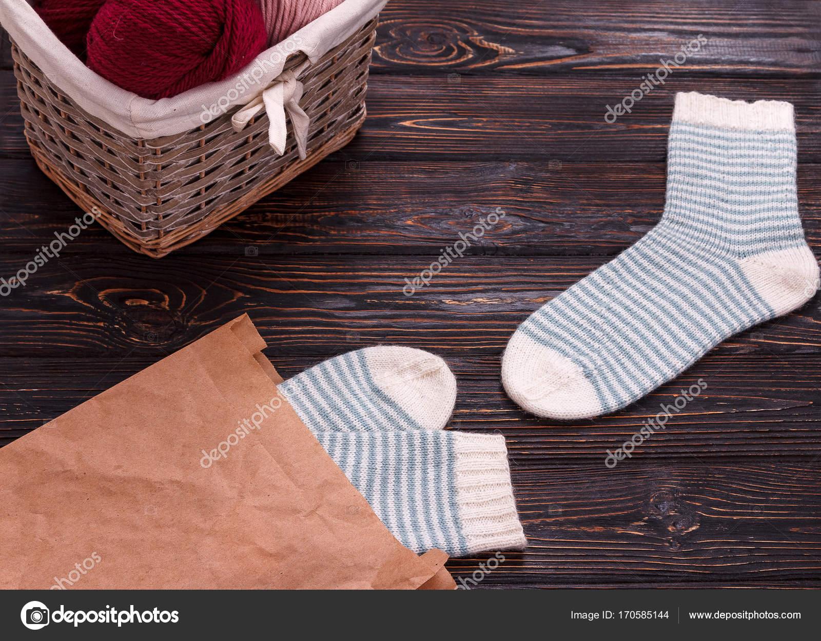 Calcetines de punto y canastilla con hilo sobre fondo de madera ...