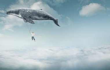 man and big whale flying over clouds