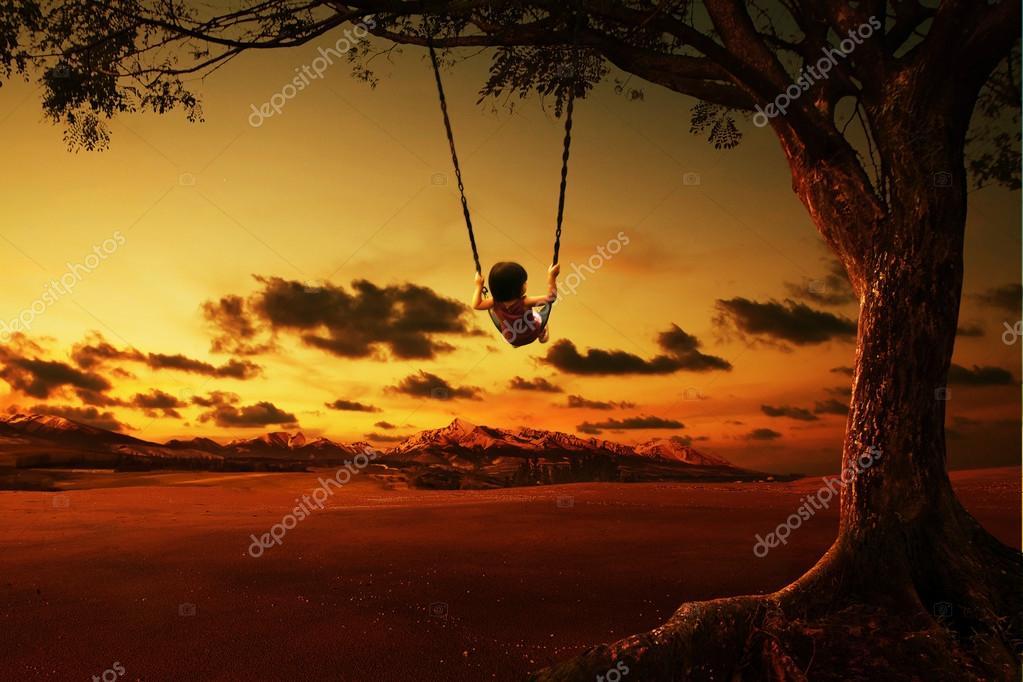 silhouette of happy little girl on swing