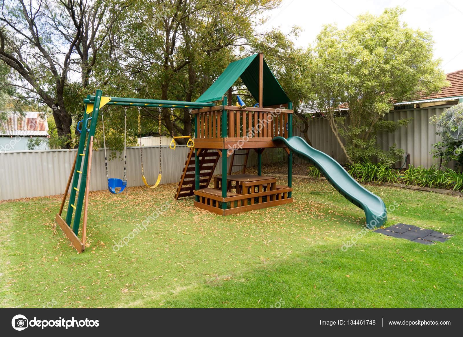 Parco giochi per bambini nel giardino di casa verde — Foto Stock © jamesteohart #134461748