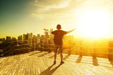 Silhouette man raise hands up for him success, beautiful cityscapes skyline view. morning sunrise scene . stock vector