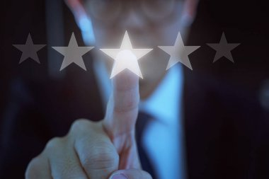 Young businessman touch the five star symbol to increase rating of company .