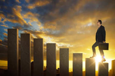 Businessman climbing stairs with sunset or sunrise background . Ambitions and success concept .
