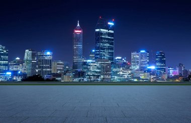 Empty square ground floor with city skyline background. Night scene .