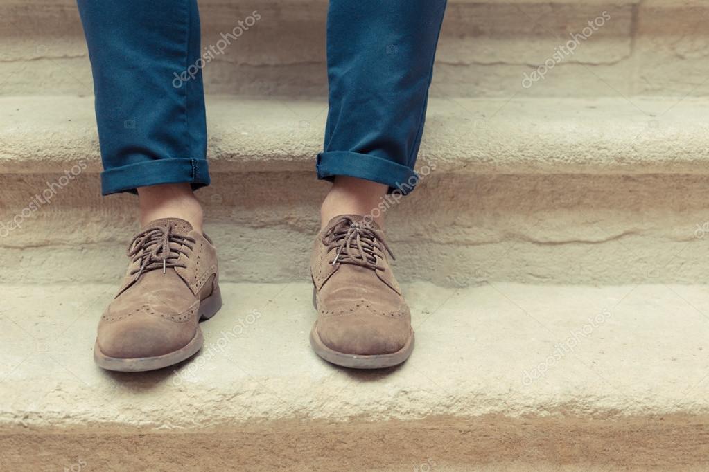 7920f7cef Hombre joven que llevaba zapatos de gamuza marrón con pantalones azul y  suite piedras del fondo en un día nublado. Sentado el chico hipster con  viejos ...