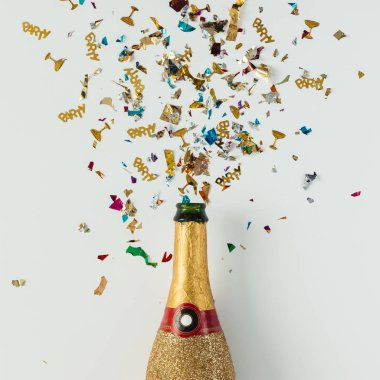 Golden champagne party bottle with confetti
