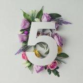 Kreativních rozložení s květinami a číslo pět
