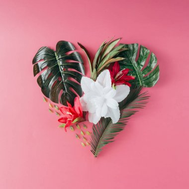 Tropical leaves and flowers in shape of heart