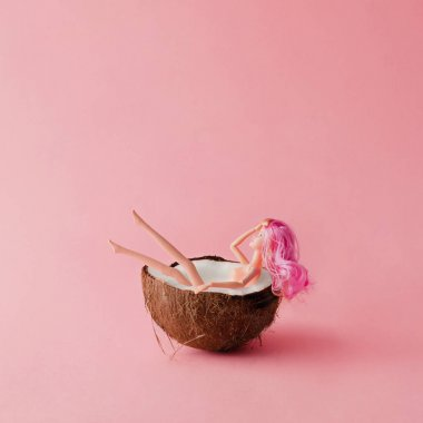 Doll with pink hair bathing in coconut