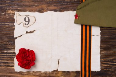 Burning sheet of paper on the table, with a red carnation and number 9,