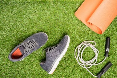 running shoes and skipping rope for training , on a grass background