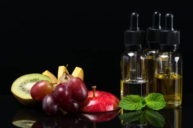 Fruit flavors liquids for electronic cigarettes, concept on a black background