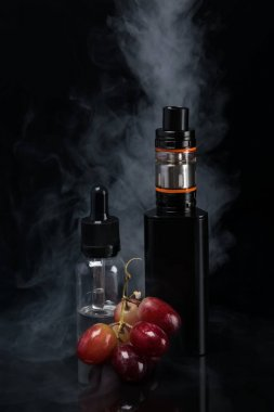 the concept of electronic cigarettes with grape on a background of smoke
