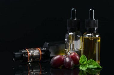 Set for vaping with grapes aroma in bottles, on a dark background