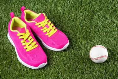 Pink sneakers and ball lie on green grass
