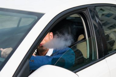 young man in a blue jacket smokes an electronic cigarette while driving a car