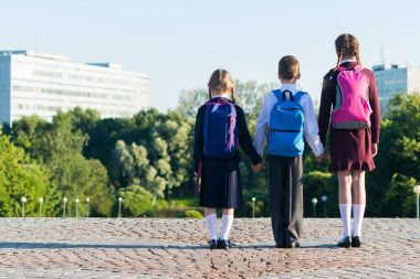 Three pupils in school uniform stand on the street with backpacks, rear view