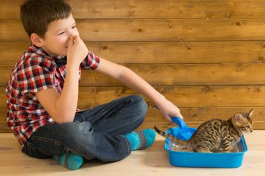 The boy closes his nose, removes the toilet behind the kitten