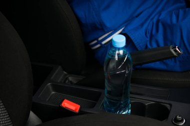 In a car in a cup holder there is a bottle of water, for the driver at the wheel