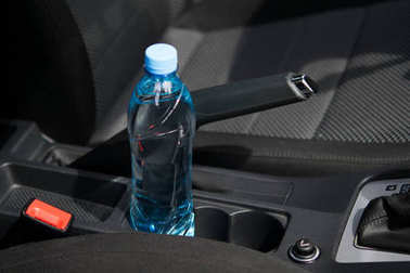 In the car in the cup holder there is a bottle of water, for the driver