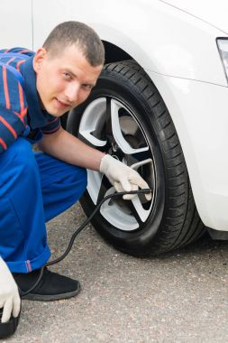 the master of tire fitting inflates the wheel of the car with a pump