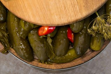 wooden barrel with pickled cucumbers and spices, covered with a lid