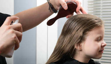 young girl doing a hairdress, wetting her hair, she smiles