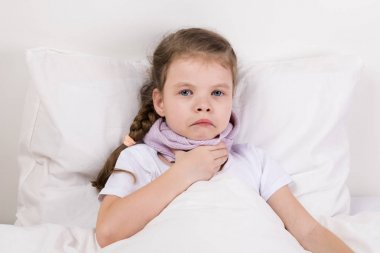 a little sick girl lies in bed and holds a hand in a sore throat, tied up with a scarf