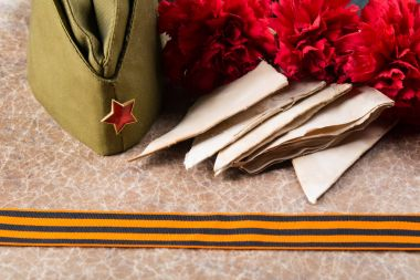 a military cap with old letters, a St. George ribbon and carnations, against a texture background with an inscription