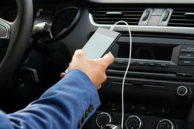 the driver of the vehicle, holds in his hand the phone connected by a white wire, to the car's music system