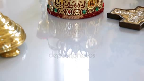 Gold crown on the table. Church wedding. Various accessories for the wedding in the church in Ukraine
