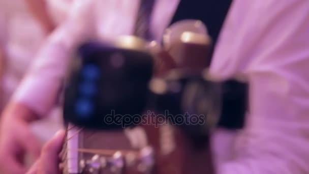 Hudebník na jevišti hraje na kytaru. Zblízka prsty dotýkat řetězce
