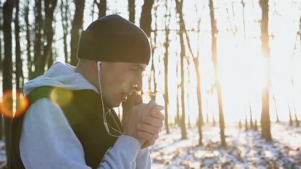 wärmt sich der junge Athlet beim Wintertraining bei Sonnenuntergang die Hände