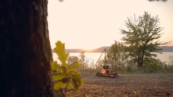 Dolly mozgást: Főzés tűz a vállalat a naplemente. Egy öntöttvas edényben át a tó tűz. Előkészítés, főzés szabadban.