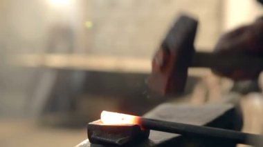 Close-up blacksmith who shapes hot steel with a hammer