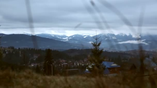Spring in the mountains, partly snow. Snow, clouds and mountains. Evening clouds cover buildings