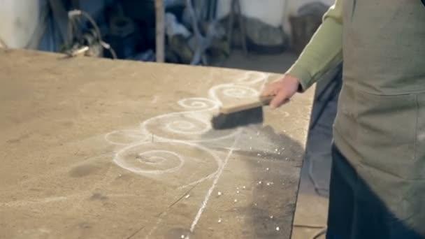 Detail muž v zástěře zametání prachu z tabulky