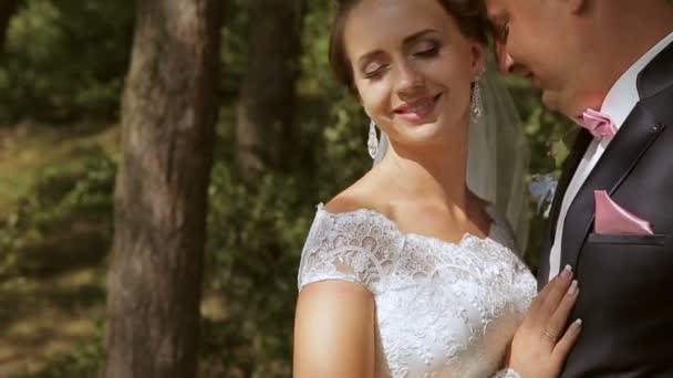Gyönyörű esküvői pár a parkban. Néhány pillanatig gyengédség. Ők ölelni egymást. Közeli kép:
