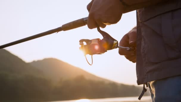 Fisherman with spinning on the lake. Sunlight through a fishing reel