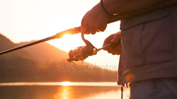 Rybář chytí rybu. Rukou rybáře s prut v ruce closeup. Spin rybářský naviják