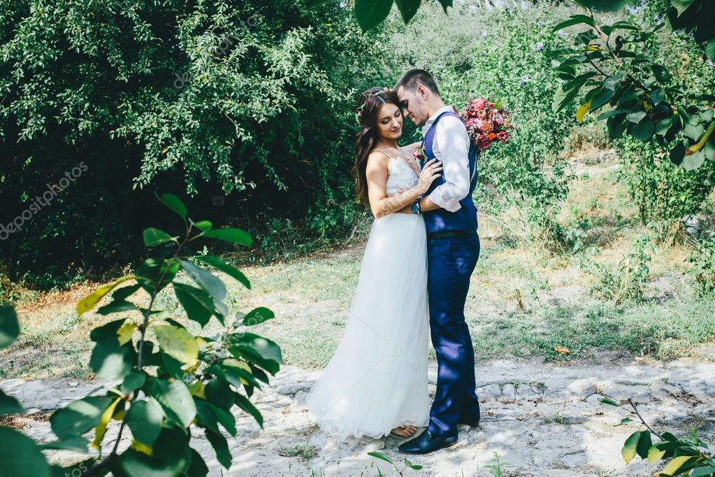 Happy groom in a dark blue suit hugs a beautiful bride in a white happy groom in a dark blue suit hugs a beautiful bride in a white wedding dress with pink and purple bouquet of flowers outdoors photo by skvalval mightylinksfo