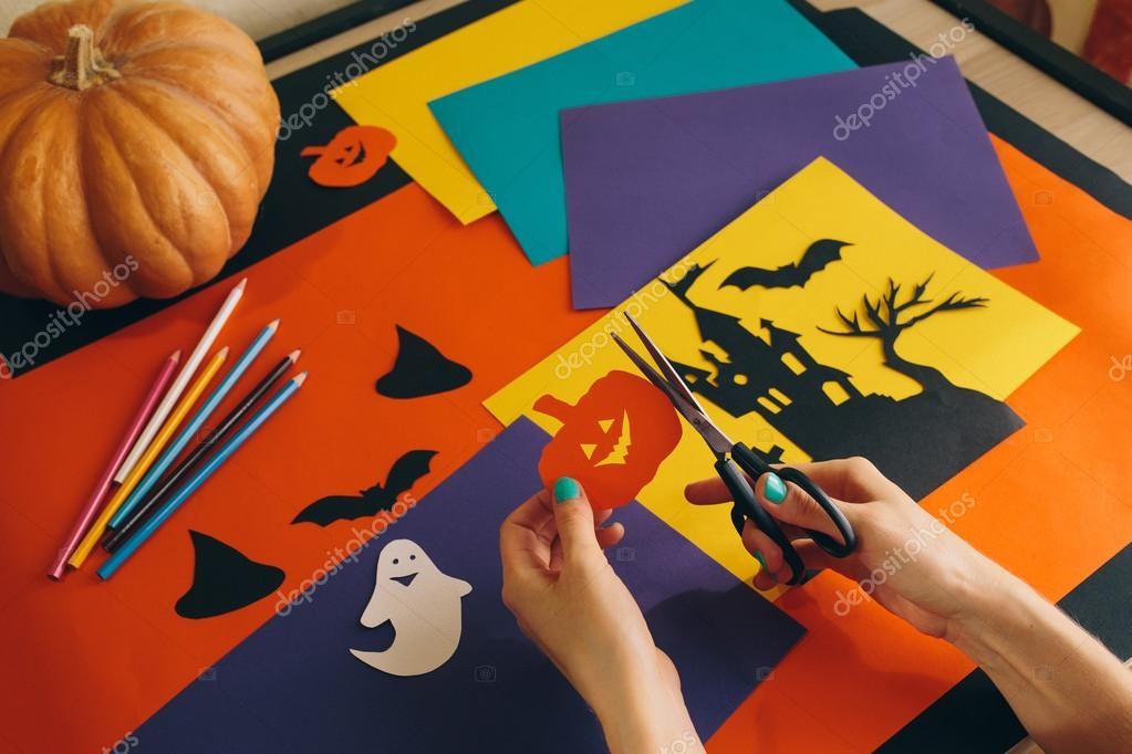 Close Up Female Hands With Scissors Cut Paper Pumpkin On The